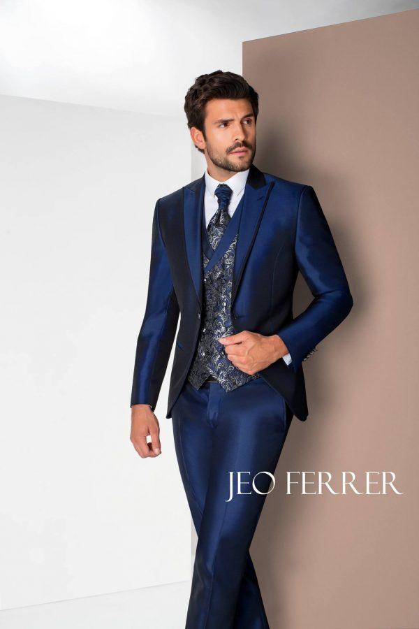 traje de novio azul eléctrico brillante con chaleco y corbata con estampado en tonos dorados