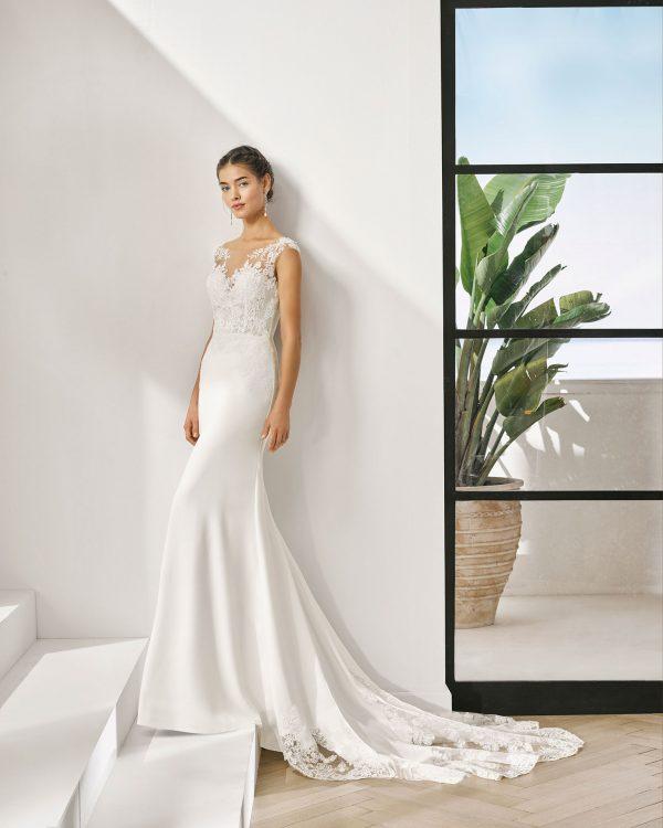 Vestido de novia corte recto de encaje y crep elástico. Escote barco y espalda en V.